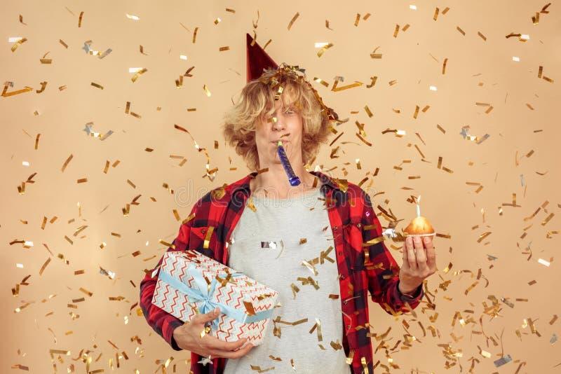 Joven celebrando el cumpleaños en la fiesta con confetti imagen de archivo libre de regalías