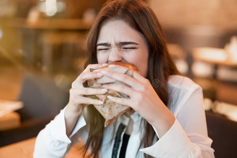 Joven con blusa blanca y elegante mordiendo con apetito de hamburguesa de carne fresca durante el almuerzo en un restaurante mode foto de archivo