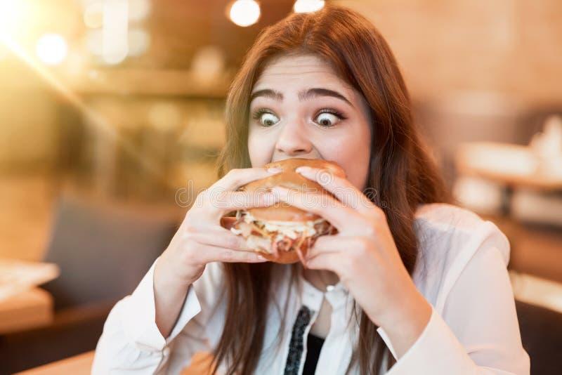 Joven con blusa blanca y elegante mordiendo con apetito de hamburguesa de carne fresca y sabrosa durante el almuerzo en una cafet fotos de archivo