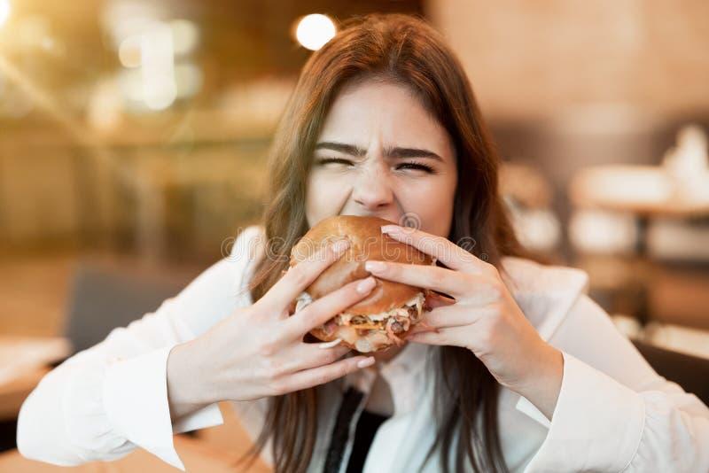 Joven con blusa blanca y elegante mordiendo con apetito de hamburguesa fresca sabrosa durante el almuerzo en el café de moda sens imágenes de archivo libres de regalías