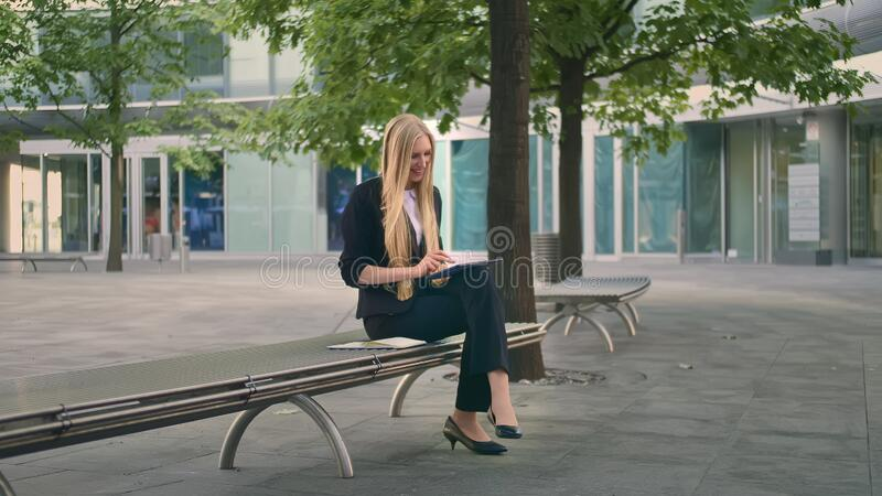 Joven con el comprimido en la banca Mujer de negocios formal sentada en el patio de la oficina y tableta de navegación en tiempo  foto de archivo libre de regalías