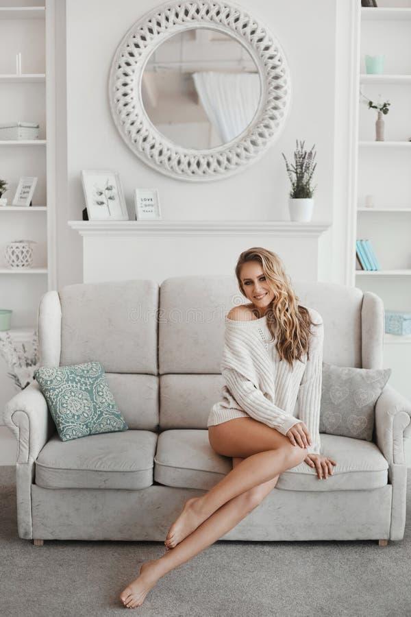 Joven con largas piernas sexys y pelo rubio en suéter blanco posando en el sofá en un acogedor apartamento por la mañana imagenes de archivo