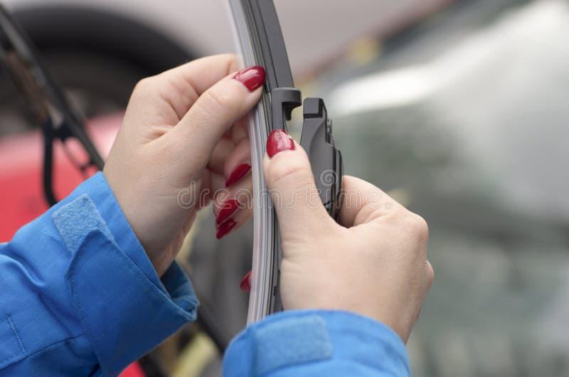 Joven con uñas rojas se prepara para poner un nuevo cepillo para limpiaparabrisas de auto fotografía de archivo