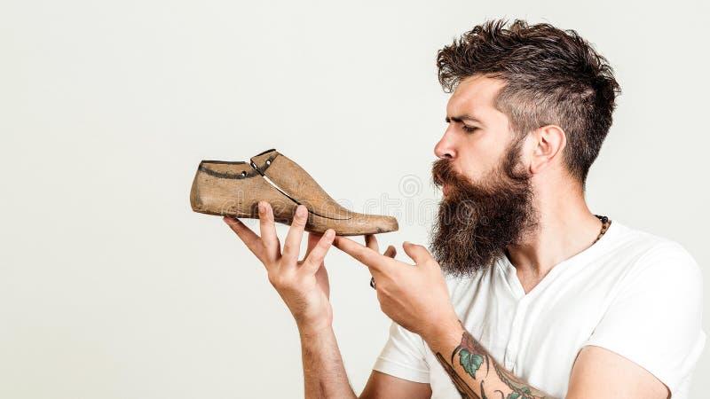 Joven diseñador sosteniendo un último zapato de madera sobre fondo blanco Idea creativa del nuevo modelo de zapatos Se prepara un imagenes de archivo