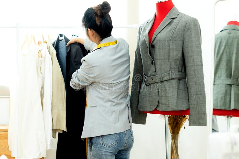 Joven diseñadora de moda asiática trabajando en su diseñador en la sala de exposición, Lifestyle Stylish tomando medidas sobre imagen de archivo