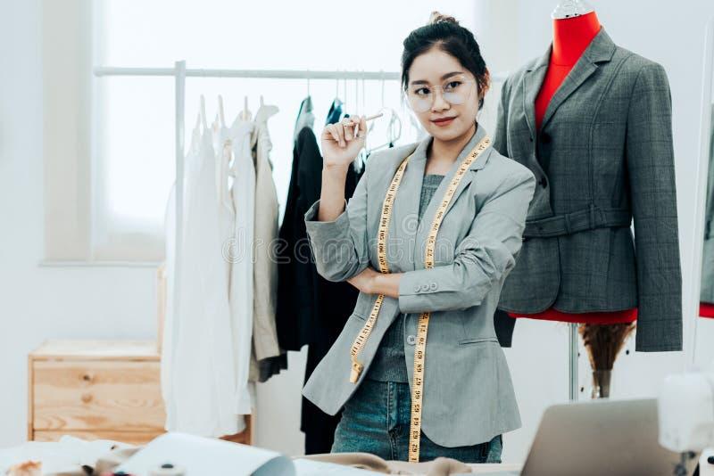Joven diseñadora de moda asiática trabajando en su diseñador en la sala de exposición, Lifestyle Stylish tomando medidas sobre fotos de archivo