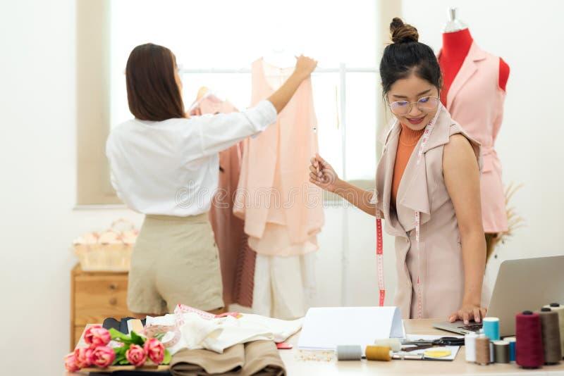 Joven diseñadora de moda asiática trabajando y llevando a una clienta a la sala de exposición imagen de archivo