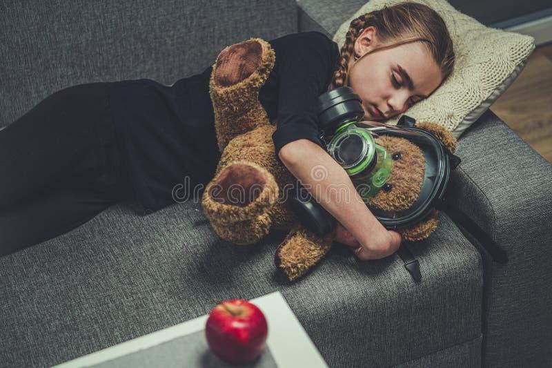 Joven durmiendo en el oso de juguetes Sofa con máscara de gas fotografía de archivo
