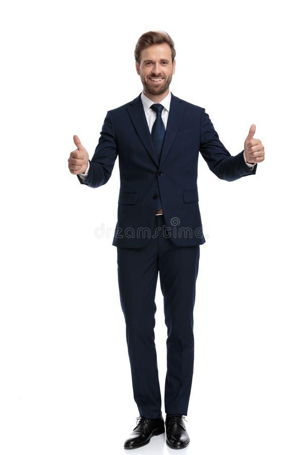 Joven empresario sonriente haciendo pulgares arriba fotografía de archivo