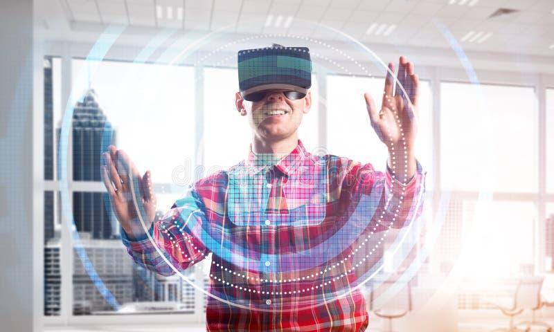 Joven en el interior de la oficina moderna experimentando la tecnología de la realidad virtual fotografía de archivo libre de regalías