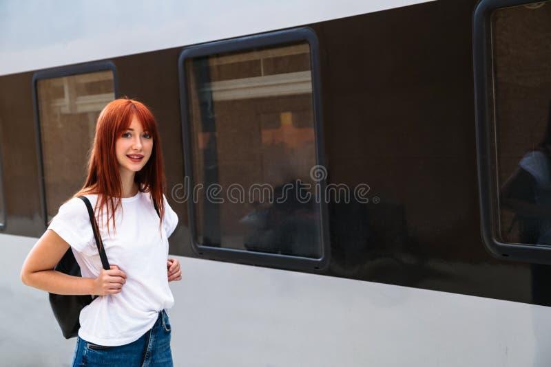 Joven en una plataforma ferroviaria cerca del tren suburbano fotos de archivo libres de regalías