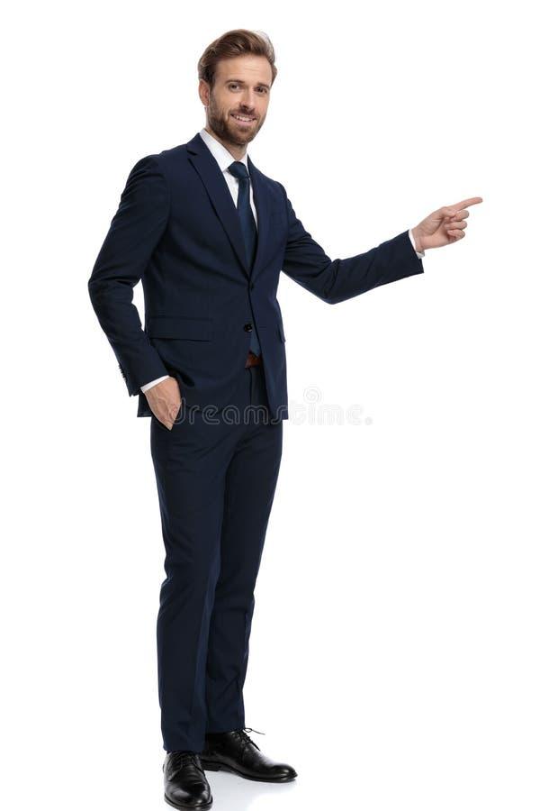 Joven hombre de negocios con traje azul marino que apunta de un lado a otro foto de archivo libre de regalías