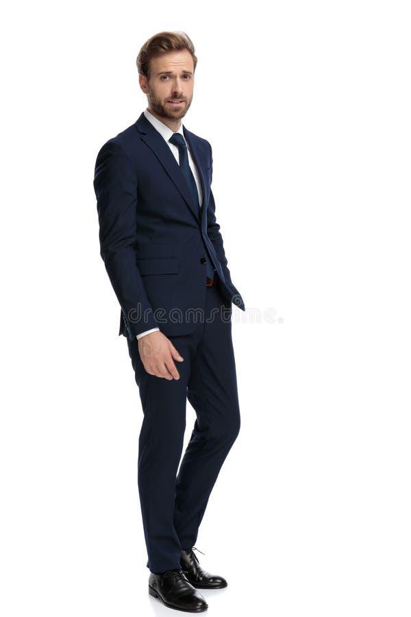 Joven hombre de negocios con traje azul marino tomándose la mano en el bolsillo imagen de archivo