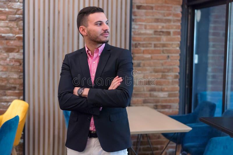 Joven hombre de negocios que está en una oficina moderna y piensa en nuevos proyectos imagen de archivo