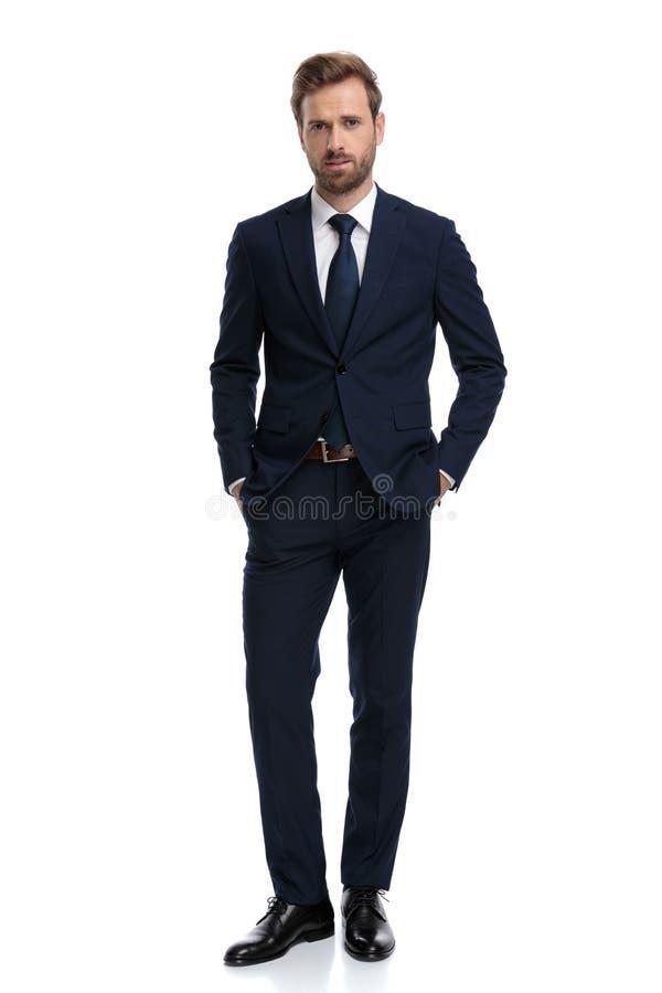 Joven hombre de negocios sexy con traje azul marino cogidos de la mano en los bolsillos fotografía de archivo libre de regalías