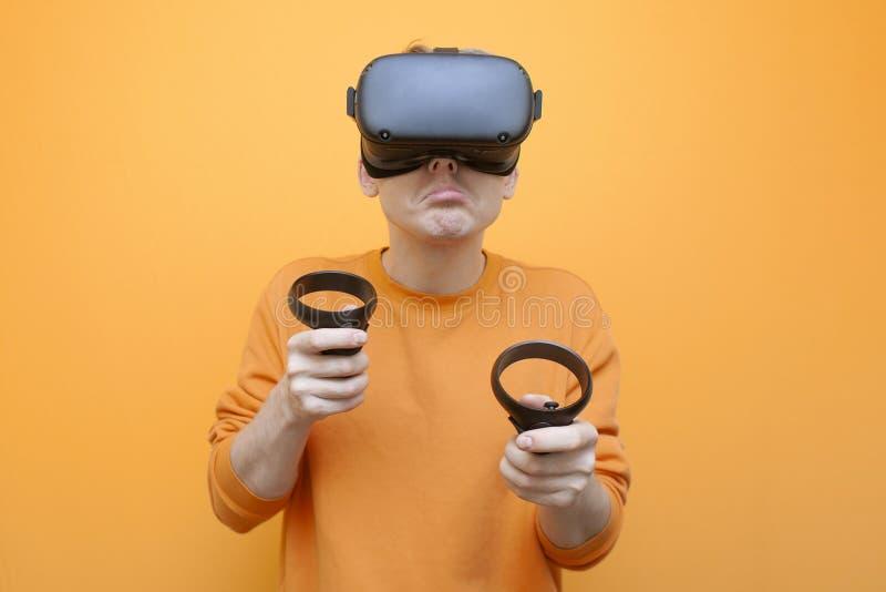 Joven hombre triste con gafas VR en un fondo naranja, un jugador sostiene joystick y juega un juego virtual foto de archivo