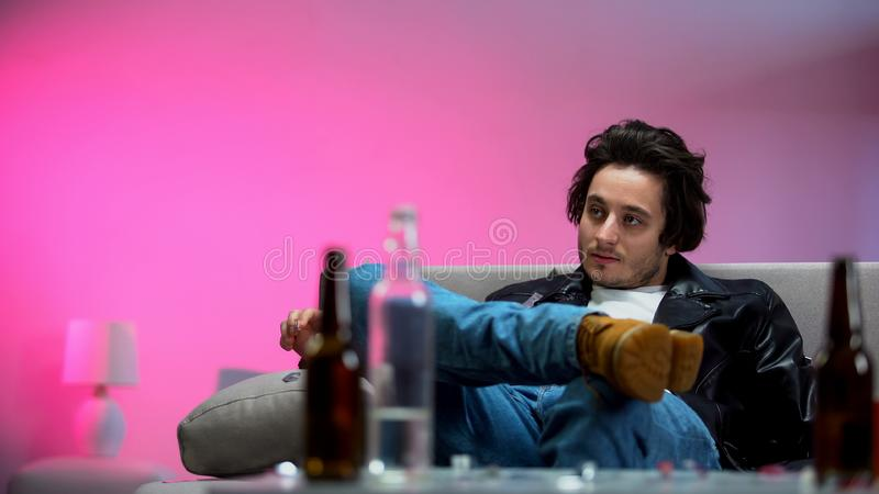 Joven intoxicado sentado en el sofá, botellas de alcohol sobre la mesa, fiesta de moda fotos de archivo libres de regalías