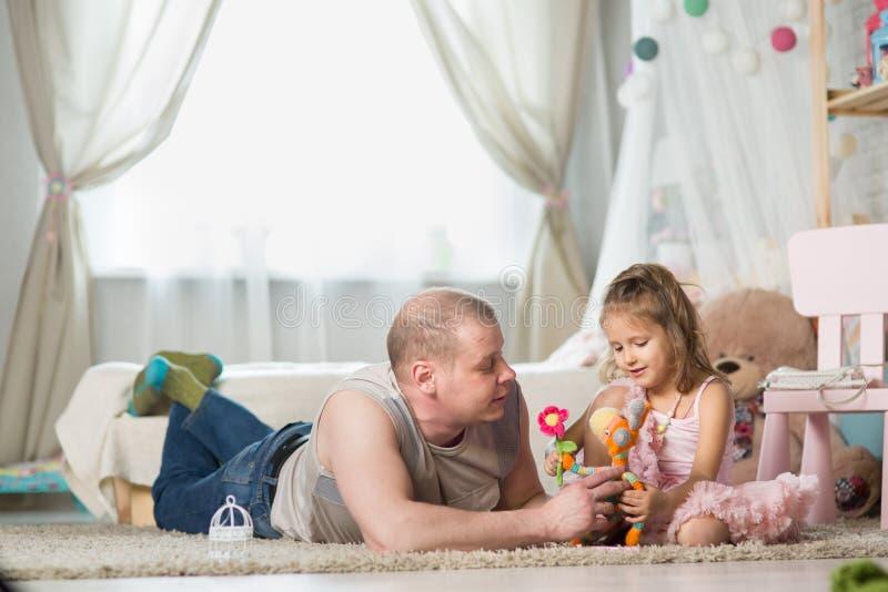 Joven jugando con su pequeña hija imagen de archivo
