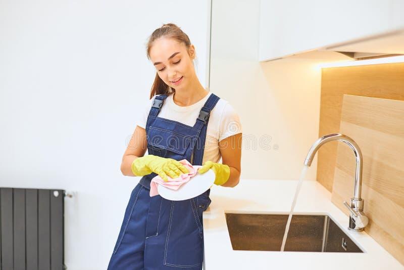 Joven limpiando platos de cerámica en la cocina imágenes de archivo libres de regalías