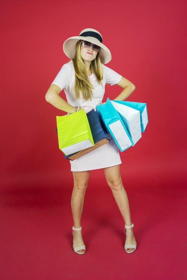 Joven llevando bolsas de compras en el estudio foto de archivo libre de regalías