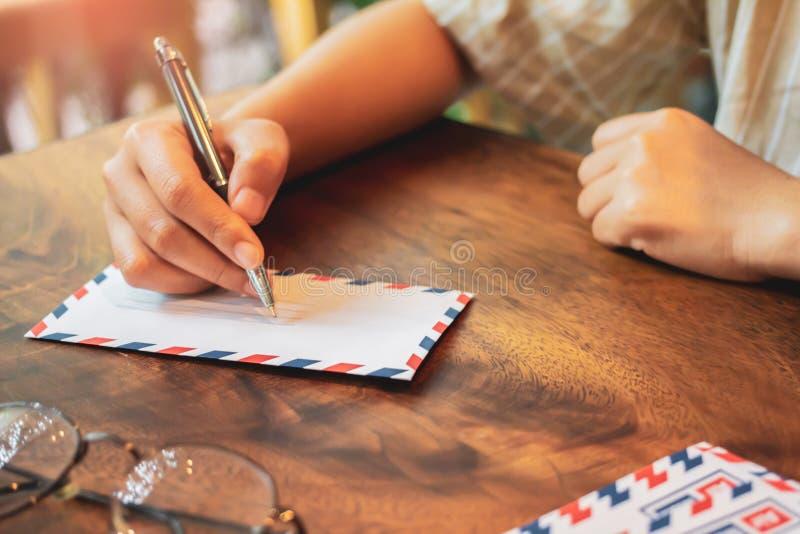 Joven mano escribiendo la carta en papel a través de la oficina de correos con nostalgia y preocupación de la familia sobre una m imágenes de archivo libres de regalías
