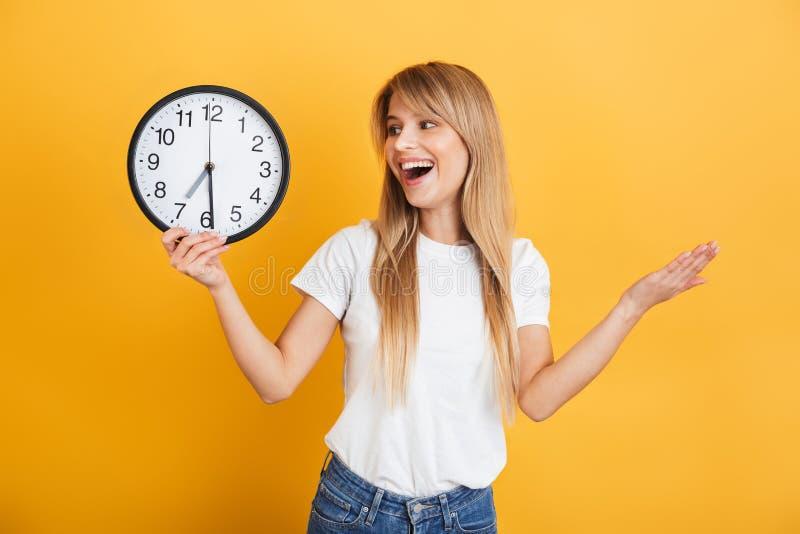 Joven mujer rubia alegre posando aislada sobre un fondo amarillo vestido con una camiseta blanca casual con un reloj foto de archivo libre de regalías