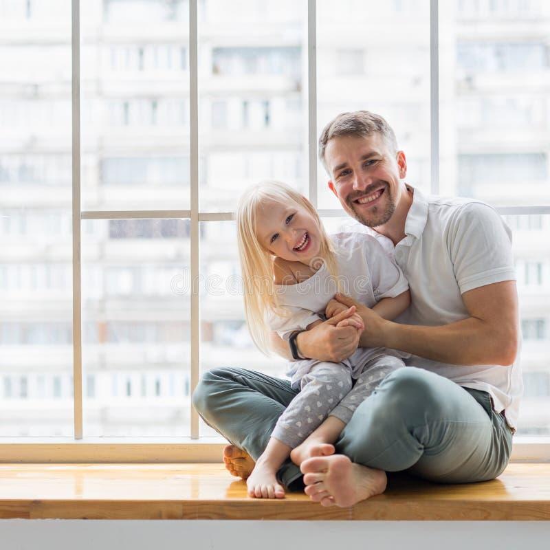 Joven padre agarrando a su hija de 3,5 años mientras está sentada en el umbral de la ventana imagen de archivo