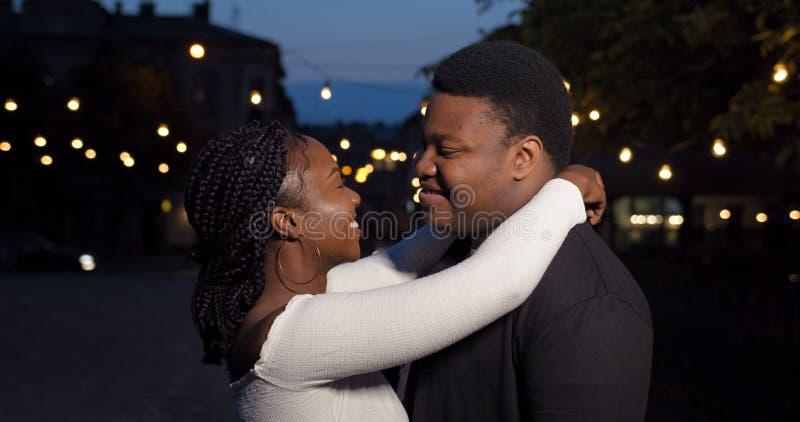Joven pareja abrazándose y buscando la cámara Cerca de un novio y una novia sonrientes parados juntos en la ciudad de la noche fotografía de archivo libre de regalías