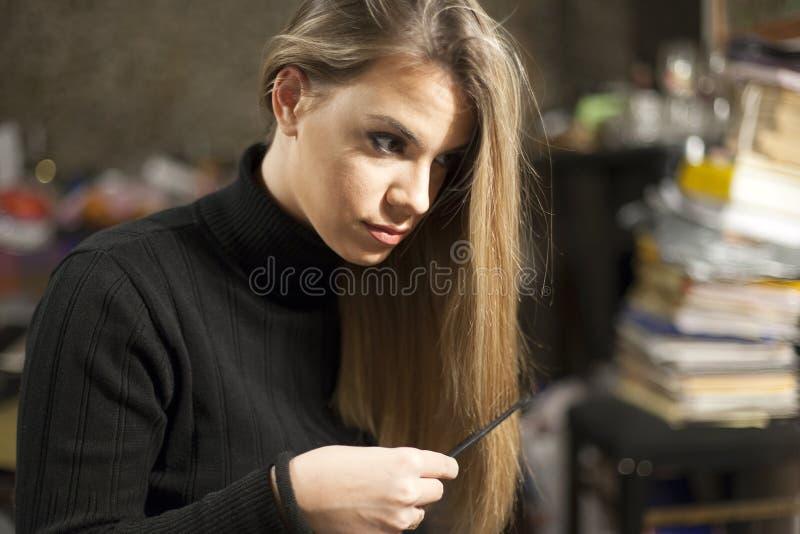 Joven peinando su pelo rubio en un lío, piel natural imagen de archivo libre de regalías