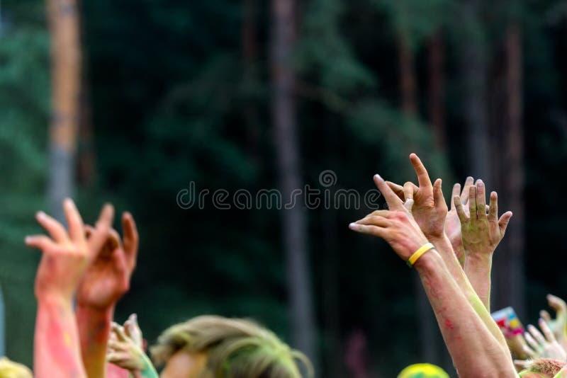 Joven sirve las manos en el aire en un fest del color con el polvo amarillo Fu imagenes de archivo