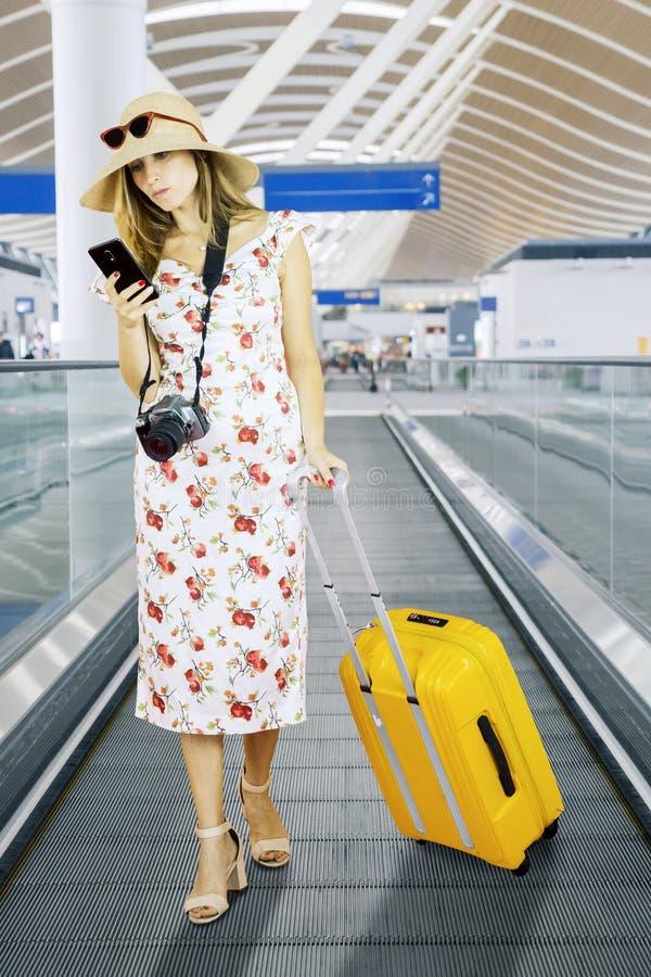 Joven turista leyendo un mensaje por teléfono en el aeropuerto fotografía de archivo libre de regalías