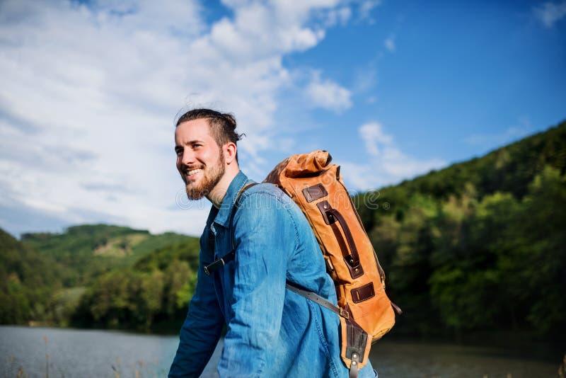 Joven turista viajero con mochila de pie en la naturaleza, descansando fotografía de archivo