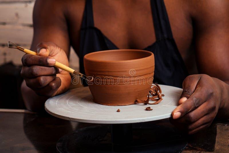 Joven y feliz hombre de negocios latinoamericano creando moldes de arcilla hecha a mano jarrón en el taller. escultor creativo fotos de archivo
