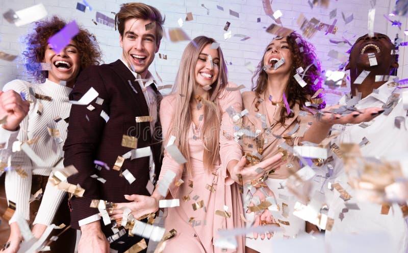 Jovenes amigos divertidos que se burlan de estar bajo un confetti en casa foto de archivo