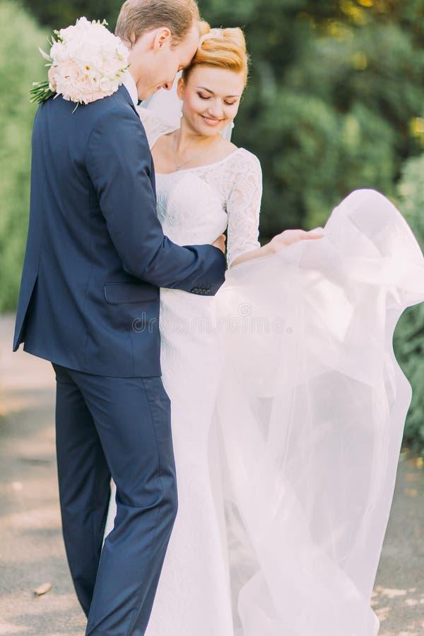 Jovenes felices tratan el novio y a la novia con suavidad que presentan en el parque Ramo nupcial de la boda de flores en manos fotos de archivo libres de regalías