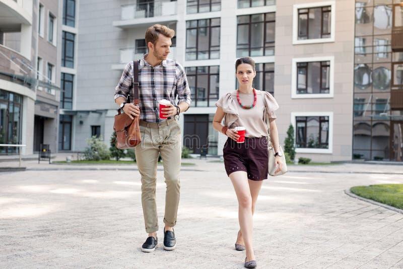 Jovens agradáveis que guardam xícaras de café fotos de stock royalty free