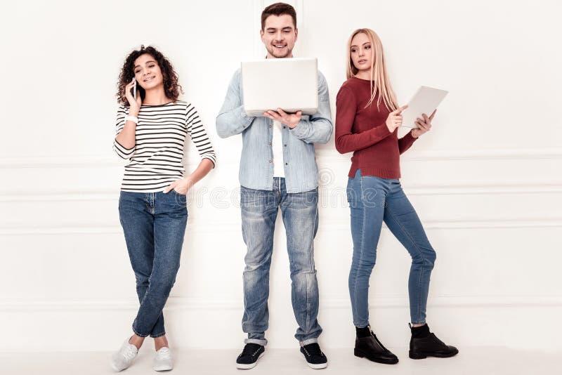 Jovens agradáveis que usam seus dispositivos imagem de stock royalty free