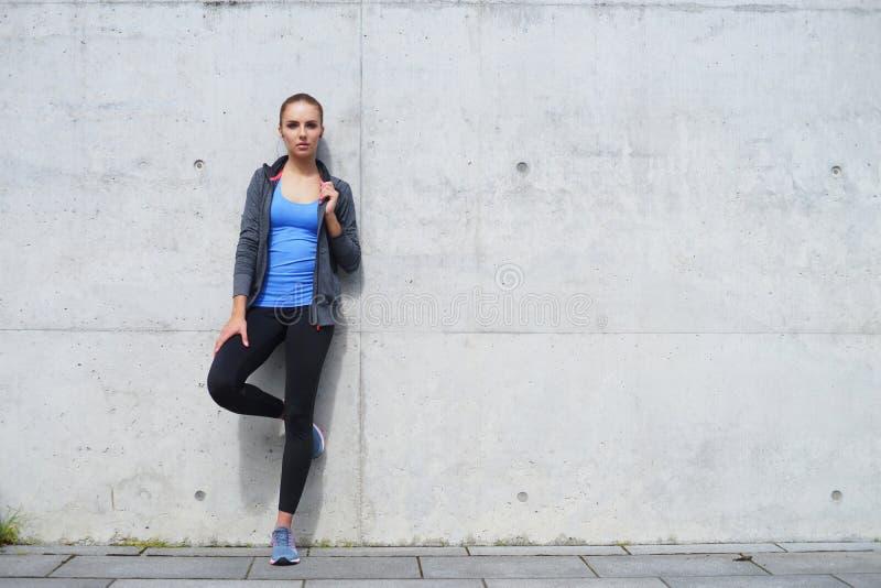 Jovens, ajuste e mulher desportiva estando na frente da parede concreta do cimento Aptidão, esporte, movimentar-se urbano e saudá foto de stock royalty free