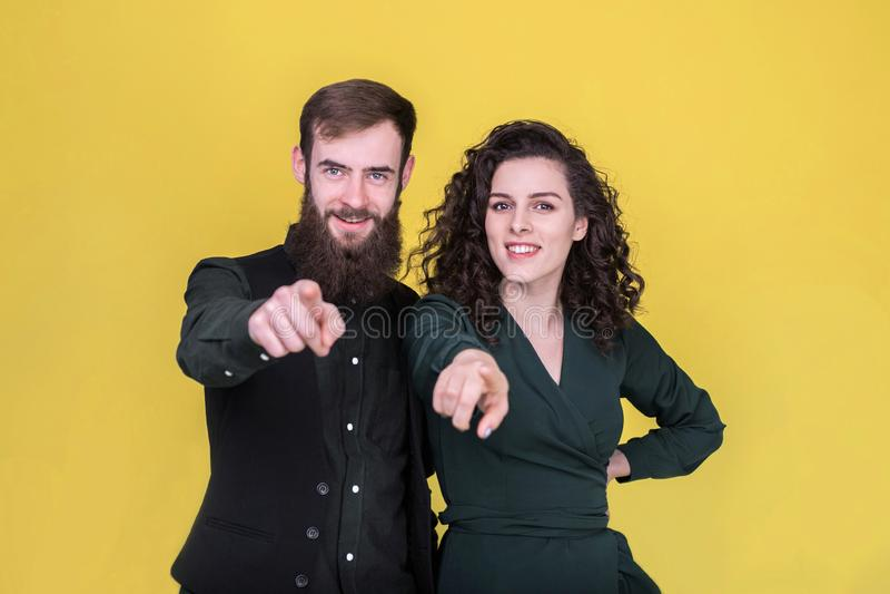 Jovens alegres que apontam os dedos na câmera fotos de stock