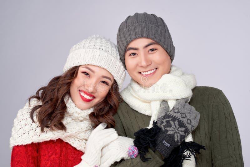Jovens amantes felizes em roupas de lã de malha abraçando e olhando juntos imagem de stock