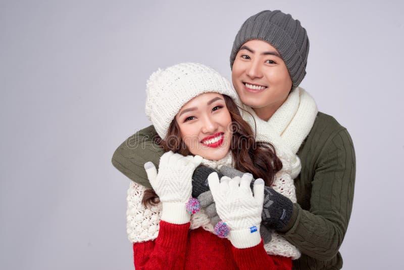 Jovens amantes felizes em roupas de lã de malha abraçando e olhando juntos imagem de stock royalty free