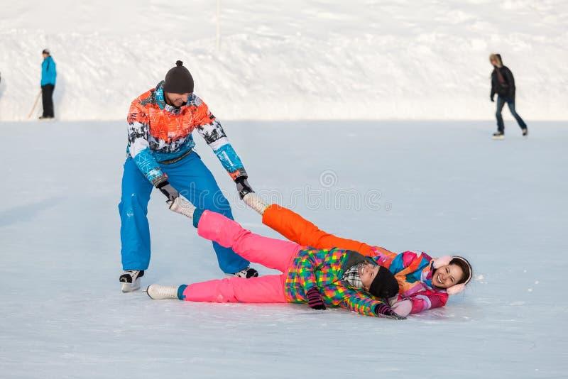 Jovens, amigos, inverno patinando no gelo no lago congelado fotografia de stock