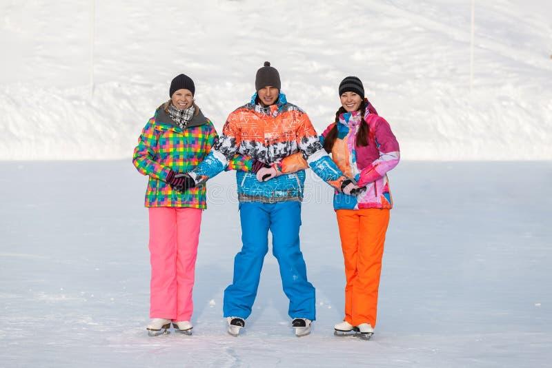 Jovens, amigos, inverno patinando no gelo no lago congelado imagens de stock