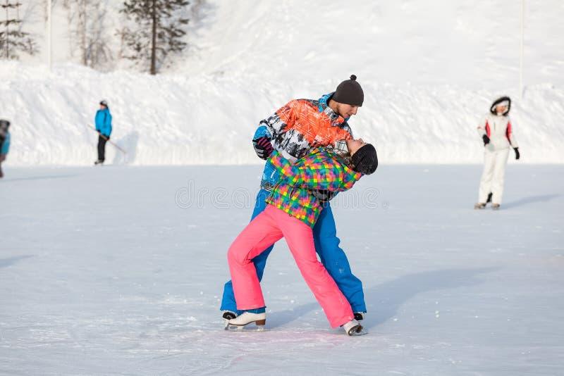 Jovens, amigos, inverno patinando no gelo no lago congelado foto de stock royalty free
