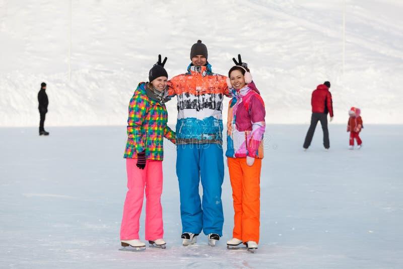 Jovens, amigos, inverno patinando no gelo no lago congelado imagens de stock royalty free