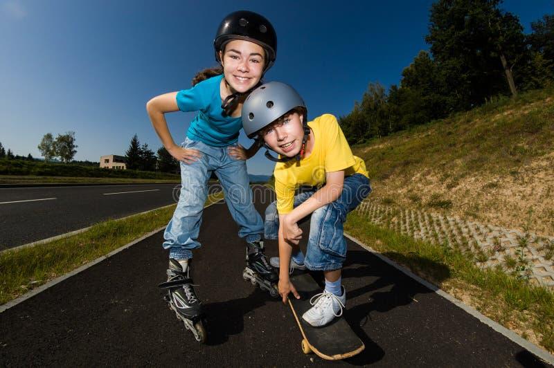 Jovens ativos - rollerblading, skateboarding fotografia de stock