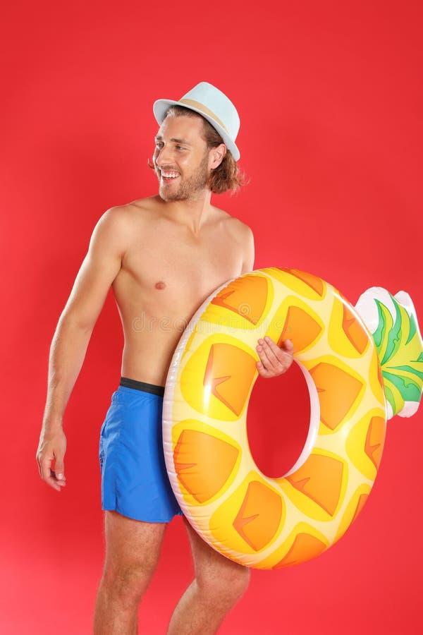 Jovens atrativos no roupa de banho com anel inflável do abacaxi no fundo vermelho foto de stock