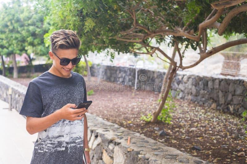 Jovens bonitos caucasianos usam celulares ao ar livre - tecnologia e conceito de conexão com a internet para viciados imagens de stock
