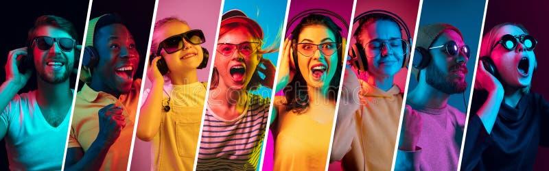 Jovens bonitos na luz de néon isolada no fundo colorido do estúdio foto de stock