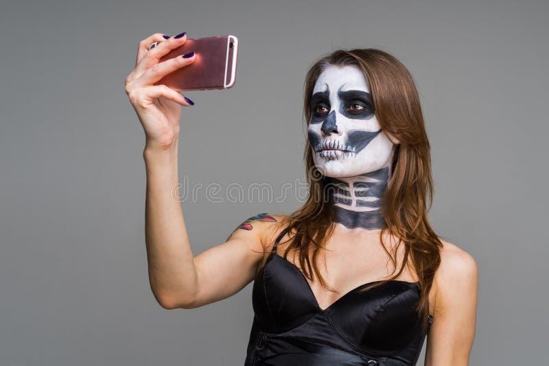 Jovens bonitos s?rios da mulher moreno com composi??o de esqueleto estarrecente do Dia das Bruxas usando o telefone esperto cor-d imagens de stock royalty free